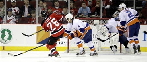 New Jersey Devils' Patrik Elias (26), of the Czech Republic, scores a goal against the New York Islanders as Mark Eaton (4), goalie Al Montoya and Mark Streit (2) defend during the first period of an NHL hockey game Tuesday, April 3, 2012, in Newark, N.J. (AP Photo/Julio Cortez)