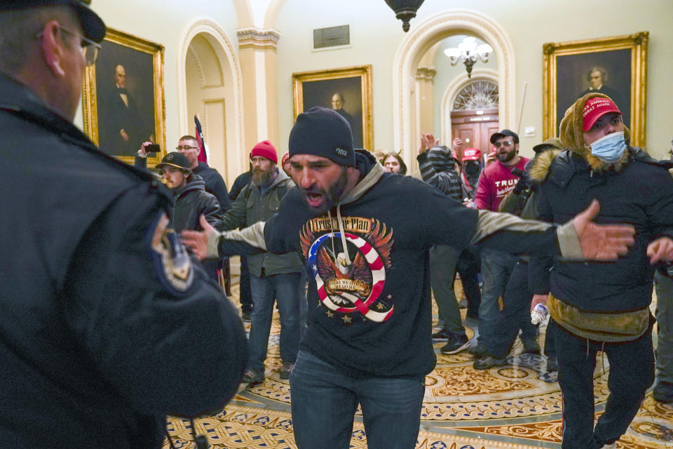 FILE - In this Jan. 6, 2021, file photo, Trump supporters, including Doug Jensen, center, confront U.S. Capitol Police in the hallway outside of the Senate chamber at the Capitol in Washington. A federal judge on Thursday, Sept. 2, 2021, ordered Jensen, a prominent participant in the Jan. 6 attack on the U.S. Capitol to return to jail after he was caught accessing the Internet to watch false conspiracy theories about the presidential election. (AP Photo/Manuel Balce Ceneta, File)
