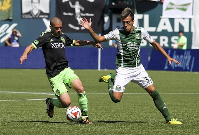 Portland Timbers' Maximiliano Urruti right, and and Seattle Sounders' Osvaldo Alonso, left, vie for control of the ball during an MLS soccer game in Portland, Ore., Sunday, Aug. 24, 2014. (AP Photo/Natalie Behring)