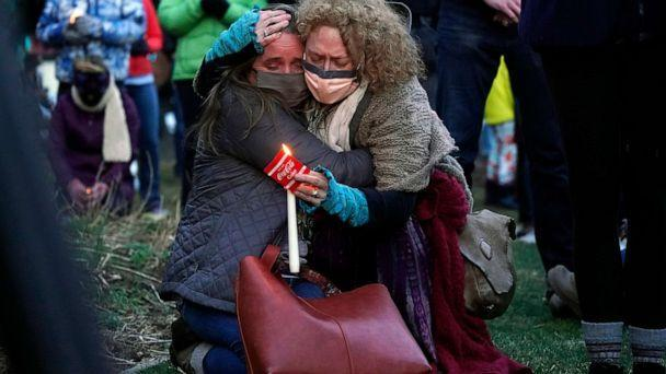 PHOTO: Mourners embrace at a vigil for the victims of a mass shooting at a grocery store earlier in the week, March 24, 2021, outside the courthouse in Boulder, Colo. (David Zalubowski/AP)