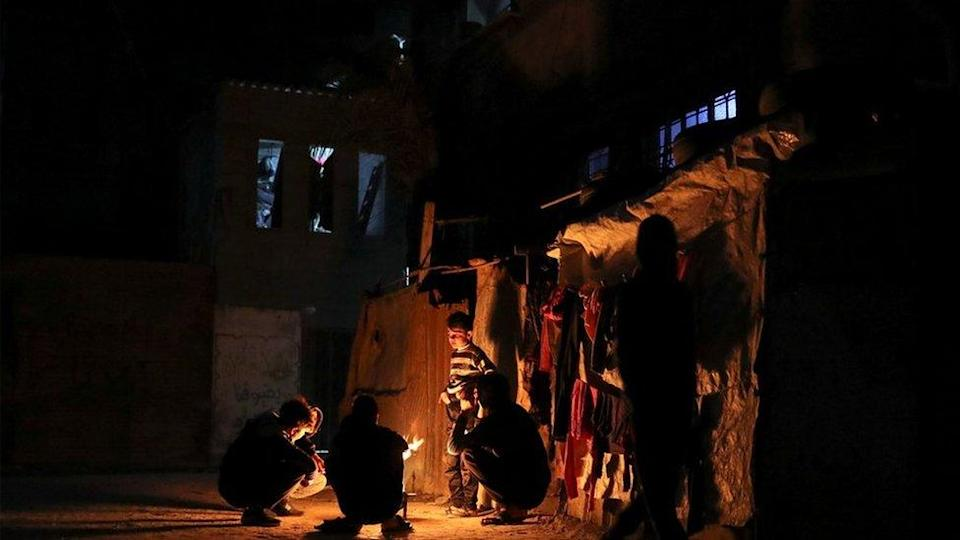 Boys warming themselves round a fire - power cuts are a regular occurrence in Gaza