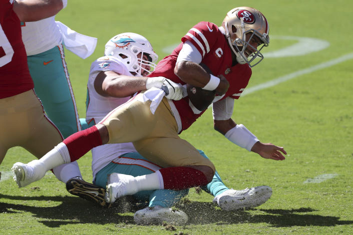 Miami Dolphins defensive end Zach Sieler, left, sacks San Francisco 49ers quarterback Jimmy Garoppolo. (AP Photo/Jed Jacobsohn)