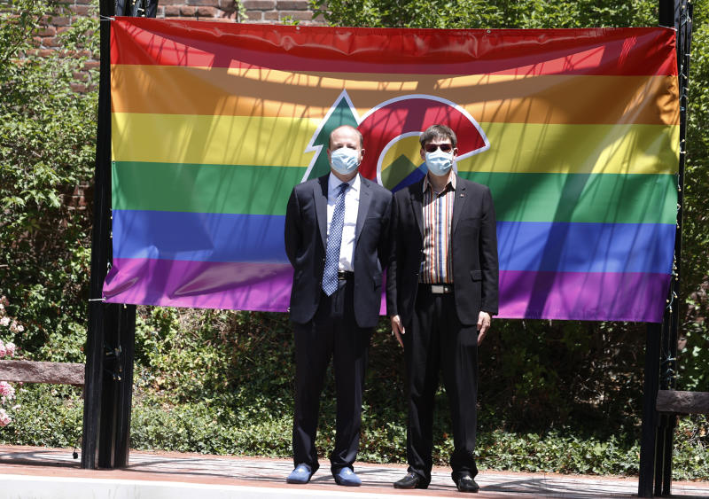 Colorado Gov. Jared Polis, left, and the state's first gentleman, Marlon Reis, pause in front of a pride flag in the garden of the Governor's Mansion on the way into a news conference about the state's efforts to cut the spread of the new coronavirus Tuesday, June 30, 2020, in Denver. (AP Photo/David Zalubowski)