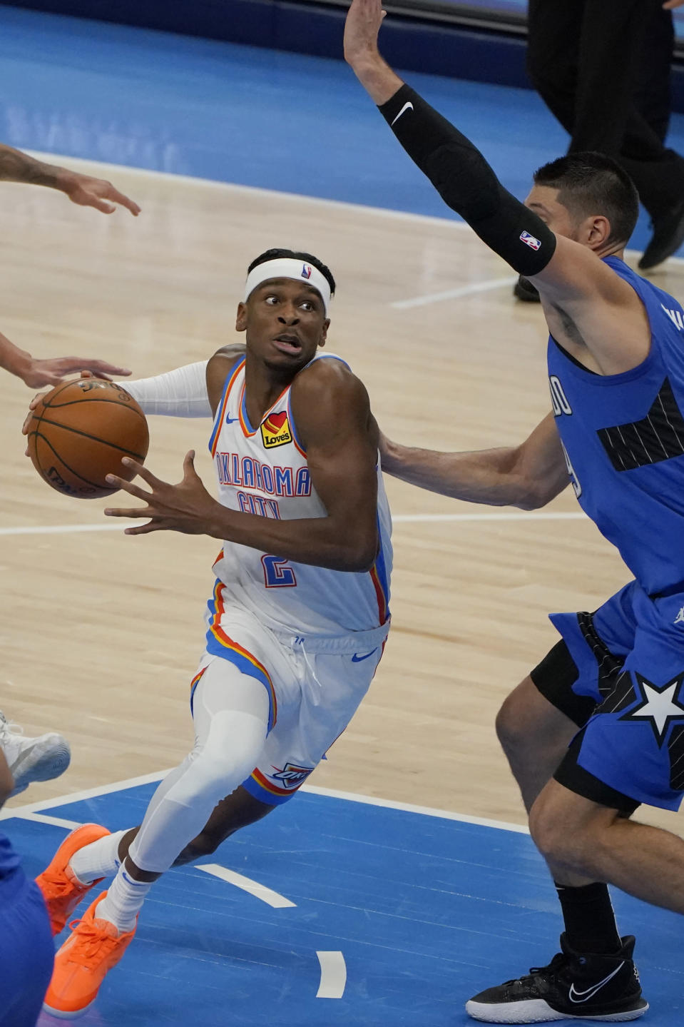 Oklahoma City Thunder guard Shai Gilgeous-Alexander (2) drives around Orlando Magic center Nikola Vucevic during the second half of an NBA basketball game Tuesday, Dec. 29, 2020, in Oklahoma City. (AP Photo/Sue Ogrocki)