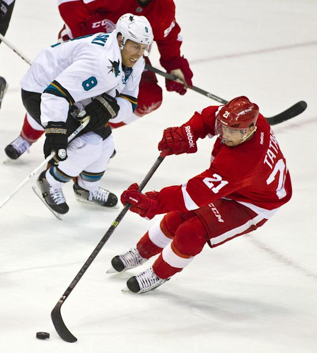 San Jose Sharks forward Joe Pavelski (8) pursues Detroit Red Wings forward Tomas Tatar (21) with the puck, during the second period of an NHL hockey game in Detroit, Mich., Monday, Oct. 21, 2013. (AP Photo/Tony Ding)