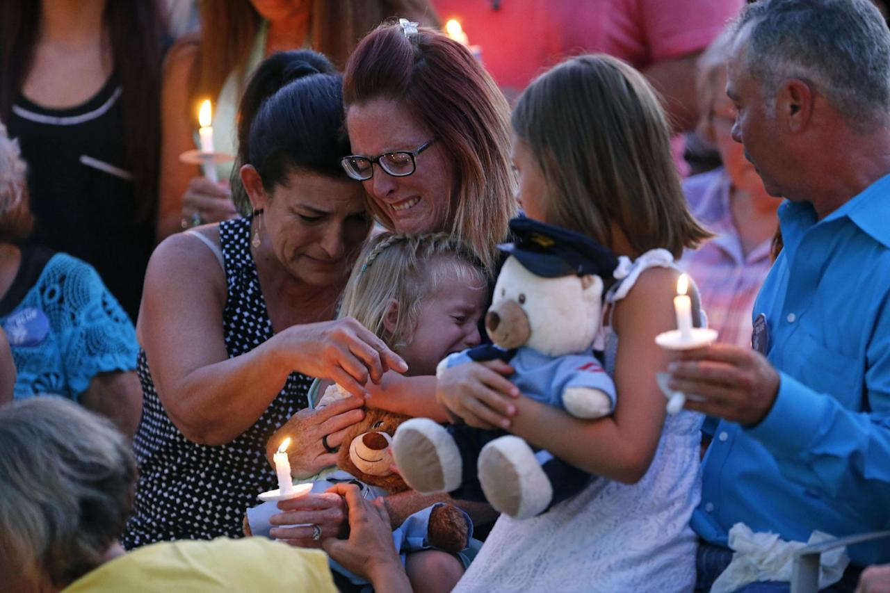 Dechia Gerald, wife of slain Baton Rouge police officer Matthew Gerald, cries while holding their children Fynleigh, left, and Dawclyn, right, during a candlelight vigil at the Healing Place Church in Baton Rouge, La., Monday, July 18, 2016. At Left is Dechia's mother, Denna Badeaux. Multiple police officers were killed and wounded Sunday morning in a shooting near a gas station in Baton Rouge. (AP Photo/Gerald Herbert)