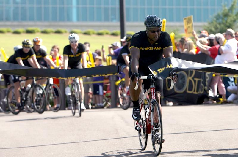 Bo Jackson, right, crosses the finish line to end his statewide bicycle journey at the Tuscaloosa Amphitheater, Saturday, April 28, 2012, in Tuscaloosa, Ala. Jackson's arrival marked the end of his 300-mile journey across the state, raising funds and awareness for the communities ravaged by the April 2011 tornadoes. (AP Photo/Tuscaloosa News, Dusty Compton)