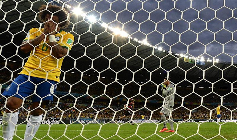 Brazil's defender Marcelo reacts after Germany scored during the semi-final football match between Brazil and Germany at The Mineirao Stadium in Belo Horizonte during the 2014 FIFA World Cup on July 8, 2014