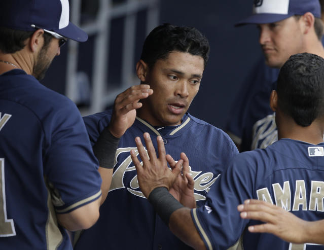 San Diego Padres' Everth Cabrera is congratulated by Xavier Nady, left, and Alexi Amarista after scoring during the first inning of a spring exhibition baseball game against the Kansas City Royals Wednesday, March 26, 2014, in Peoria, Ariz. (AP Photo/Darron Cummings)