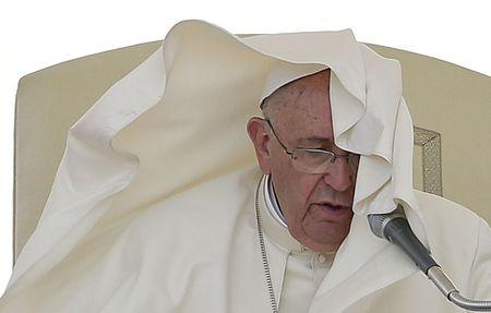 A gust of wind blows the mantle of Pope Francis as he leads his Wednesday general audience in Saint Peter's square at the Vatican June 17, 2015. REUTERS/Max Rossi -