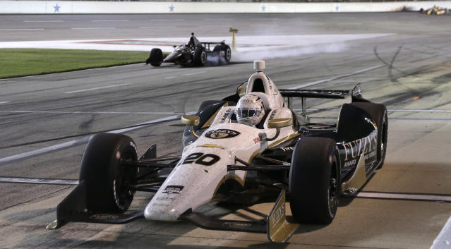 Ed Carpenter (20) pulls in for a pit stop as Will Power, of Australia, locks up his tires while slowing in the background during the IndyCar auto race at Texas Motor Speedway in Fort Worth, Texas, Saturday, June 7, 2014. Power was penalized for speeding on pit row. (AP Photo/Tim Sharp)