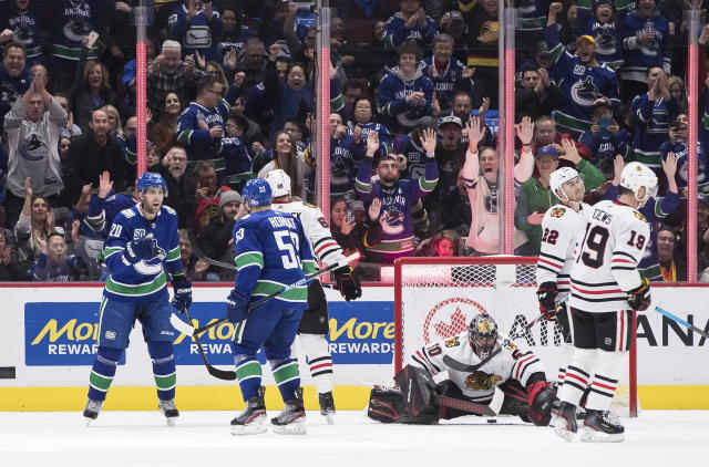Vancouver Canucks' Brandon Sutter (20) and Bo Horvat (53) celebrate Horvat's goal against Chicago Blackhawks goalie Corey Crawford (50) as Slater Koekkoek (68), Ryan Carpenter (22) and Jonathan Toews (19) skate nearby during the first period of an NHL hockey game Wednesday, Feb. 12, 2020, in Vancouver, British Columbia. (Darryl Dyck/The Canadian Press via AP)