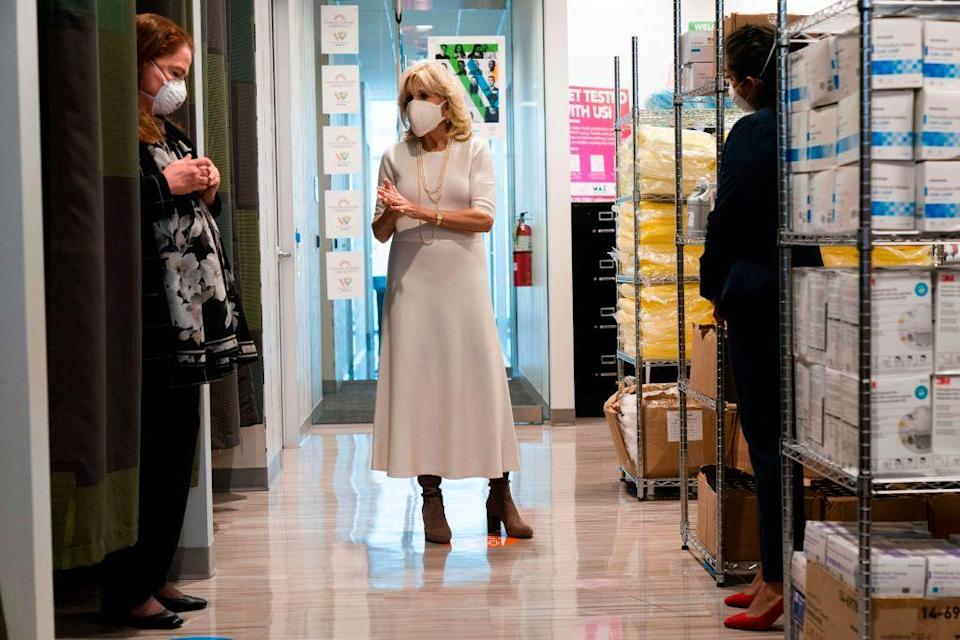 <p>For a visit to Whitman-Walker Health, the First Lady paired a simple white dress with a long, layered strand of pearls, and brown heeled boots. In keeping with her fashion choices thus far, she matched her face mask to her outfit.<br></p>