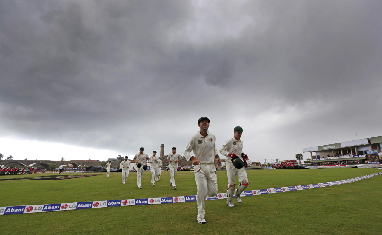 Australia's Ricky Ponting, second right, leads the team back to pavilion after umpires call off the play as dark clouds gather during the fourth day of their first test cricket match against Sri Lanka in Galle, Sri Lanka, Saturday, Sept. 3, 2011. Rain interrupted the morning session. (AP Photo/Gemunu Amarasinghe)