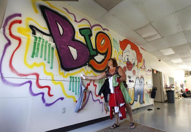 This Wednesday, Sept. 26, 2012 photo shows Tappahannock  Children's Center administrator, Ina Minter, removing coats from the front of a mural painted by rapper Chris Brown as part of his community service at the center in Tappahannock, Va. Brown has logged more than 1,400 hours of community service for the 2009 beating of former girlfriend Rihanna, basically completing his sentence. The Associated Press has learned one-third of those hours were recorded at Tappahannock  Children's Center, a rural Virginia daycare center where the singer spent time as a child and his mother once served as director. (AP Photo/Steve Helber)