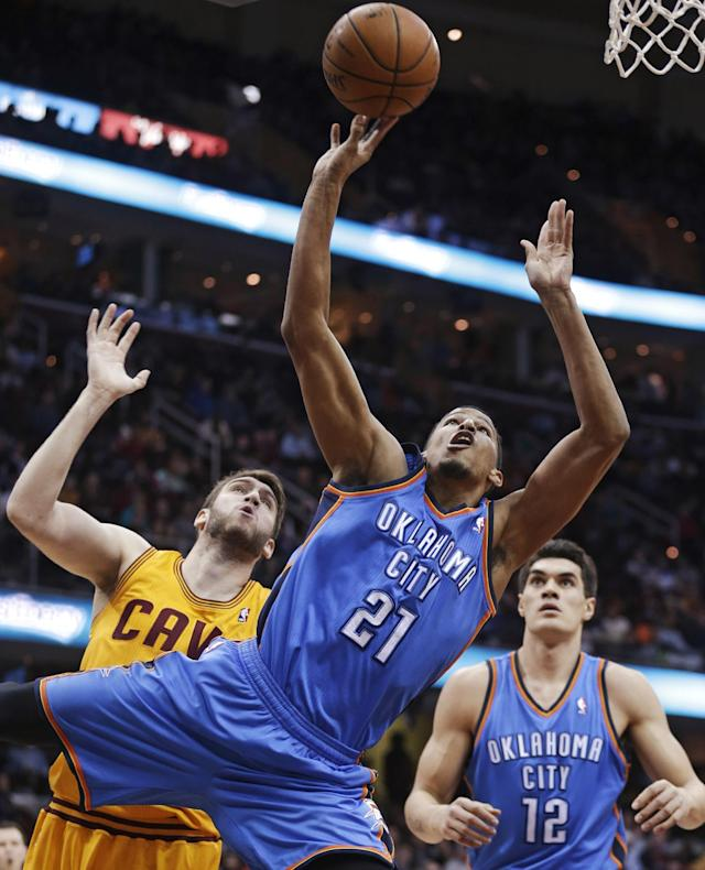 Oklahoma City Thunder's Andre Roberson, front, shoots around Cleveland Cavaliers' Spencer Hawes during the first quarter of an NBA basketball game Thursday, March 20, 2014, in Cleveland. (AP Photo/Tony Dejak)