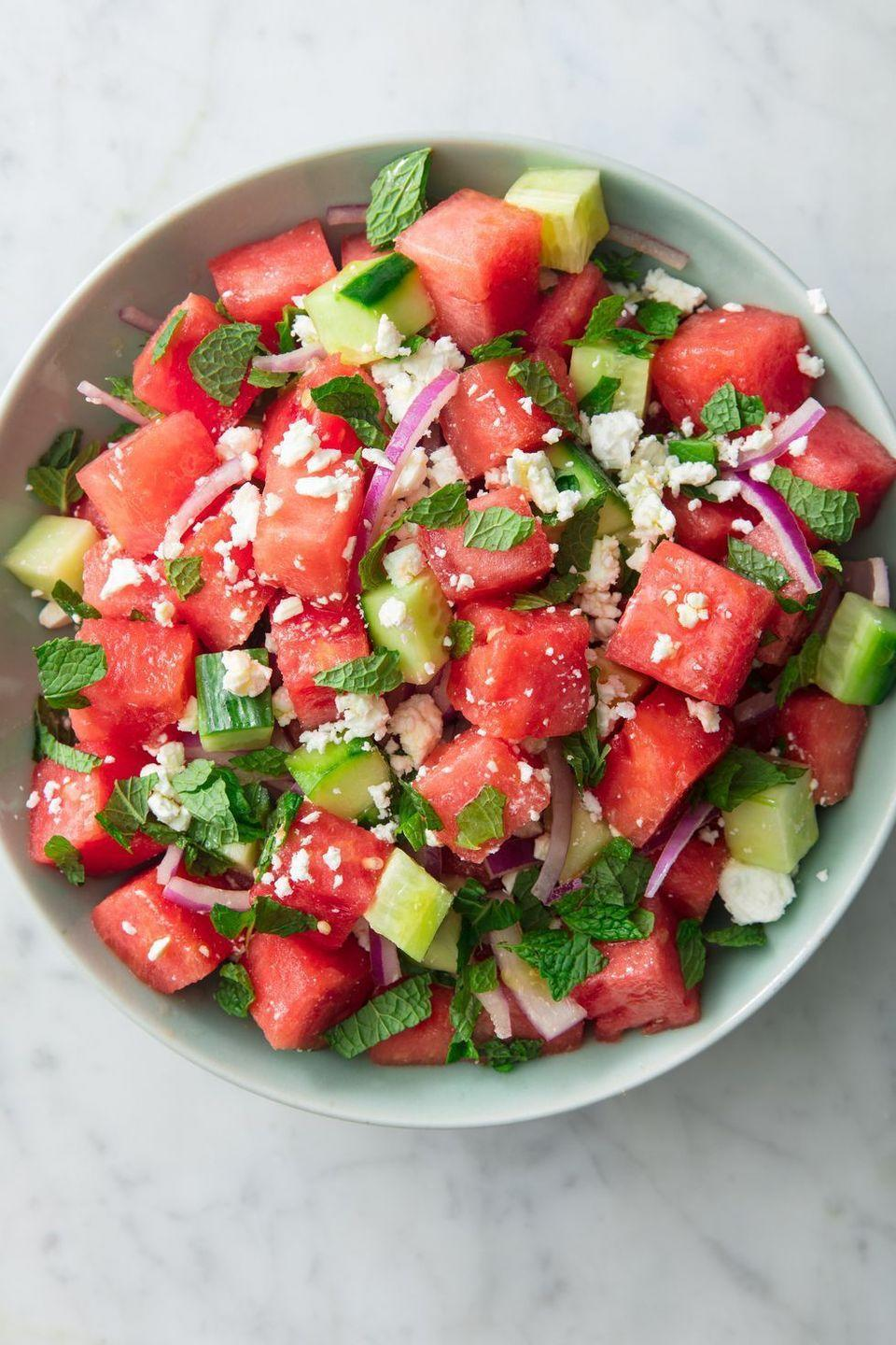 "<p>Watermelon + cucumbers is one of the most refreshing combos of all time. Throw in some mint, red onion, and feta and toss it all with a very simple vinaigrette (just olive oil + red wine vinegar), and you've got yourself a mean summer salad. </p><p>Get the <a href=""https://www.delish.com/uk/cooking/recipes/a32998257/watermelon-salad-feta-mint-recipe/"" rel=""nofollow noopener"" target=""_blank"" data-ylk=""slk:Watermelon Feta Salad"" class=""link rapid-noclick-resp"">Watermelon Feta Salad</a> recipe.</p>"