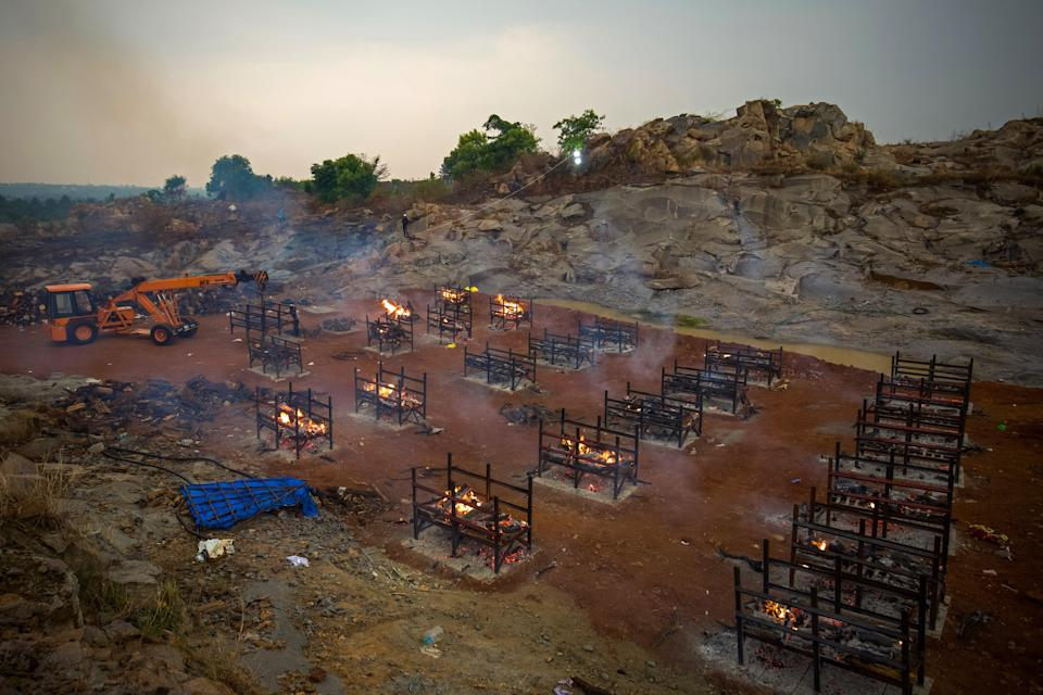 <p> A crane places new biers in a disused granite quarry repurposed to cremate the dead due to Covid-19 on April 30, 2021 in Bengaluru, India</p> (Getty Images)