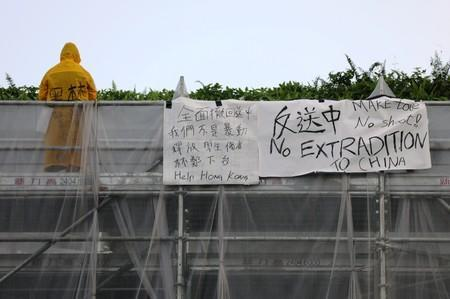 A person stands on a scaffolding surrounding the Pacific Place complex next to a banner related to the protests against the proposed extradition bill, in Hong Kong