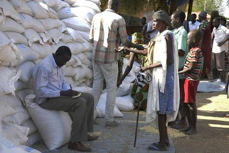 An internally displaced South Sudanese woman (R) waits to receive food aid from the World Food Programme in Bor, Jonglei state