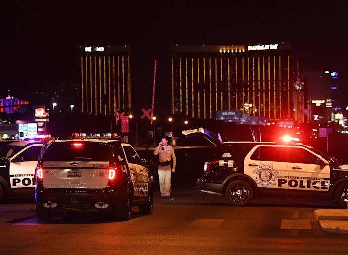 Police form a perimeter around the road leading to the Mandalay Bay Hotel (background) after a gunman killed more than 50 people and wounded more than 800 others at the festival on Oct. 1, 2017. (Photo: Mark Ralston/AFP/Getty Images)