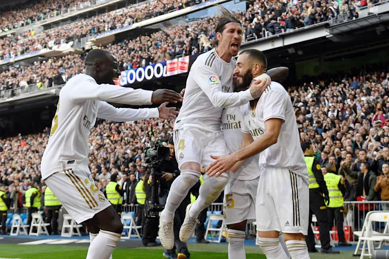 Real Madrid's French forward Karim Benzema (R) celebrates with Real Madrid's Spanish defender Sergio Ramos (C= and Real Madrid's French defender Ferland Mendy after scoring a goal during the Spanish league football match between Real Madrid CF and Club Atletico de Madrid at the Santiago Bernabeu stadium in Madrid on February 1, 2020. (Photo by PIERRE-PHILIPPE MARCOU / AFP) (Photo by PIERRE-PHILIPPE MARCOU/AFP via Getty Images)