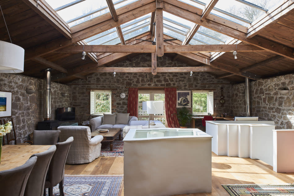 <p>One of the most impressive features is the first floor open plan living/dining room; an expansive, loft-like space with exposed solid stone walls and a partly glazed roof which floods the room with light. </p>