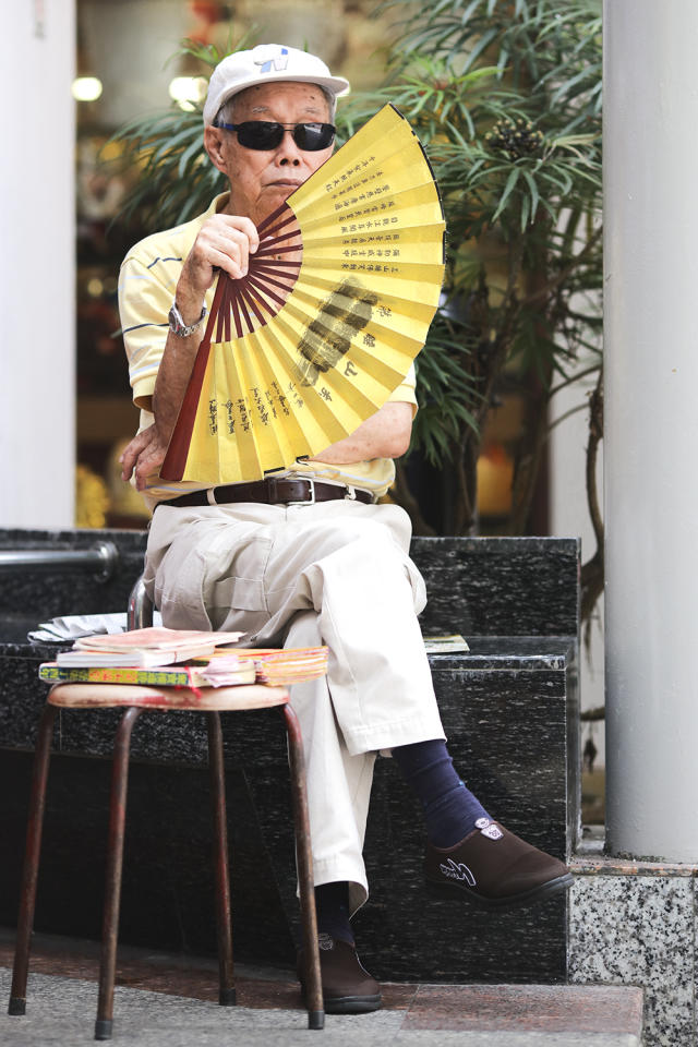 <p>Yellow polo T-shirt with long khaki pants secured with a leather belt. Complete the look with a cap, shades brown shoes and eye-catching yellow paper fan. (Photo: Don Wong) </p>