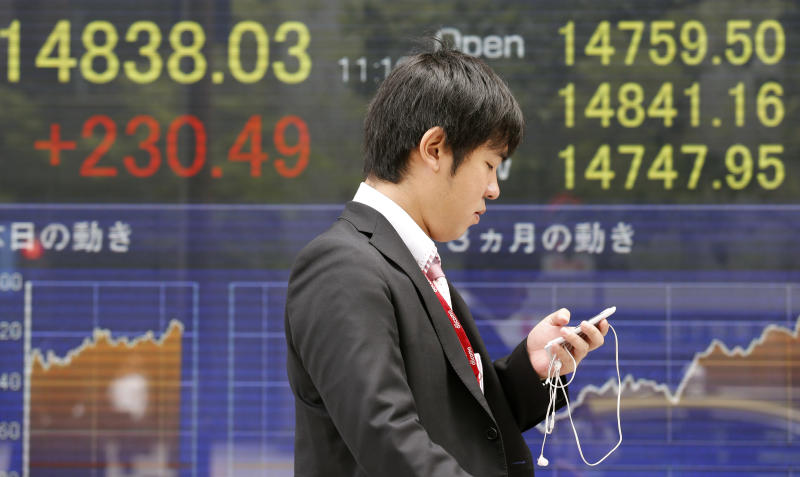 A man walks by an electronic stock board of a securities firm in Tokyo, Monday, May 13, 2013. Japan's stock market jumped Monday after global finance leaders gave a seal of approval to the country's stimulus program and refrained from criticizing its weakening effect on the yen. Stocks were mixed elsewhere in Asia. (AP Photo/Koji Sasahara)