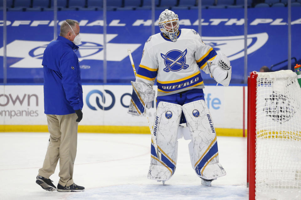 Buffalo Sabres goalie Linus Ullmark (35) is looked at by a Sabres trainer during the first period of an NHL hockey game against the New Jersey Devils, Thursday, Feb. 25, 2021, in Buffalo, N.Y. (AP Photo/Jeffrey T. Barnes)