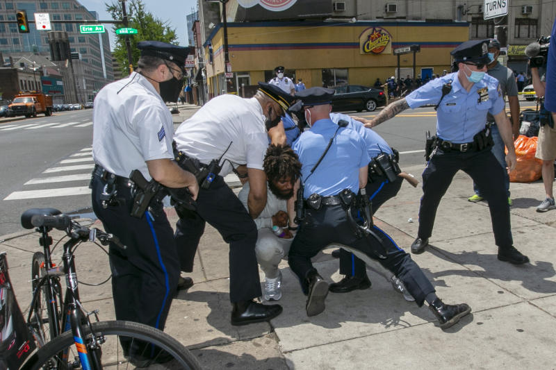 Philadelphia police tackle a man after he attacked Associated Press Photographer Matt Rourke as he was touring the business district with Philadelphia Mayor Jim Kenney and Police Commissioner Danielle Outlaw in Philadelphia on Thursday, June 4, 2020. (Alejandro A. Alvarez/The Philadelphia Inquirer via AP)