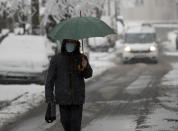A man wearing a face mask to protect against coronavirus walks through the snow covered street in Belgrade, Serbia, Monday, Jan. 11, 2021. A spate of rainy and snowy weather across the Balkans in the past days has left homes and fields flooded, disrupted road and sea traffic and caused power outages. (AP Photo/Darko Vojinovic)