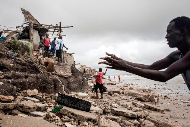 A man repairs his makeshift barrier to protect his house before the next high tide arrives in Bargny, Senegal, on Sept. 3, 2020. (Photo: JOHN WESSELS via Getty Images)