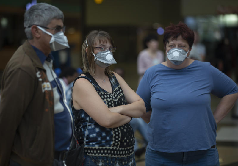 People wearing masks wait for passengers at Johannesburg's O.R. Tambo International Airport, Monday, March 16, 2020 a day after President Cyril Ramaphosa declared a national state of disaster. Ramaphosa said all schools will be closed for 30 days from Wednesday and he banned all public gatherings of more than 100 people. South Africa will close 35 of its 53 land borders and will intensify screening at its international airports. For most people, the new COVID-19 coronavirus causes only mild or moderate symptoms. For some it can cause more severe illness. (AP Photo/Denis Farrell)