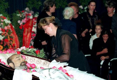 FILE PHOTO: A woman lays flowers during a funeral of Ivan Kivelidi, a prominent Russian banker and the chairman of the 'Russian Businessmen' round table organisation in Moscow, Russia  August 8, 1995. REUTERS/Alexander Natruskin/File Photo