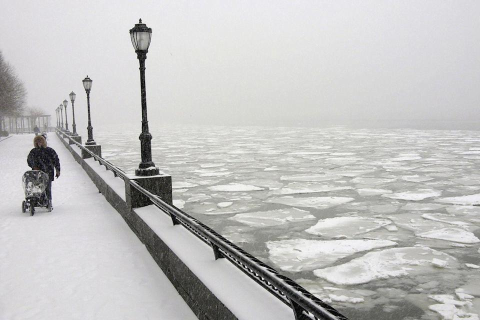 <p>A man pushes a baby buggy on a causeway along the Hudson River where ice is forming in lower Manhattan, in New York City 22 January 2005.</p>