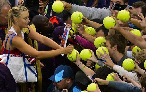 Russia's Maria Sharapova signs autographs following her victory over Israel's Shahar Peer