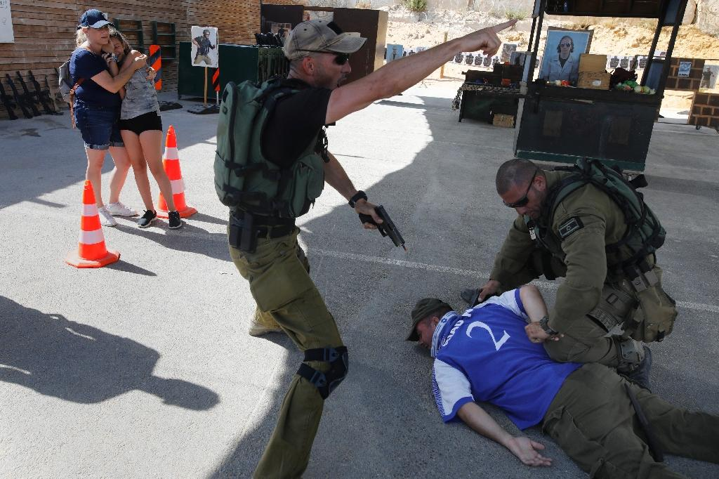 "Foreign tourists react as Israeli instructors tackle a man during a simulation of a knife attack during an ""anti-terrorism"" course in the West Bank on July 18, 2017 (AFP Photo/MENAHEM KAHANA)"