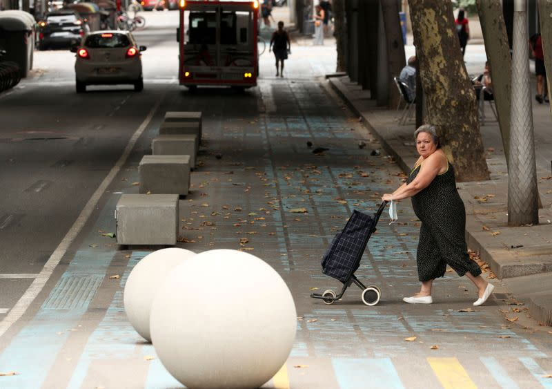 Woman walks by a pedestrian zone painted in blue and yellow at a junction in Barcelona