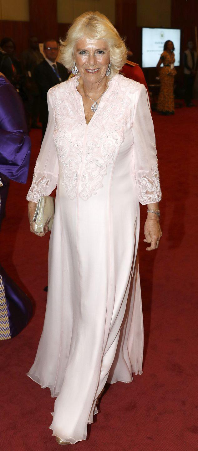 """<p>The Duchess of Cornwall stunned in an embroidered blush gown as she arrives at a State Banquet at Jubilee House in Ghana. Camilla completed the look with a gold clutch and an earring and necklace set by one of her favorite jewelers, <a href=""""https://www.vancleefarpels.com/us/en/search/search.html?prodSort=NOVE&srchSecondary=CREATIONS&isAvail=false&srchText=&srchTags=SNOWFLAKE&tokenNumber=0.22876550113044392"""" rel=""""nofollow noopener"""" target=""""_blank"""" data-ylk=""""slk:Van Cleef & Arpels"""" class=""""link rapid-noclick-resp"""">Van Cleef & Arpels</a>. </p>"""