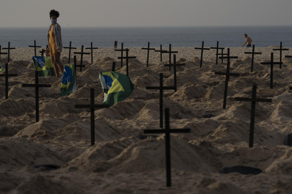 A woman walks amid symbolic graves on Copacabana beach, dug by activists from NGO Rio de Paz protesting the government's handling of the COVID-19 pandemic in Rio de Janeiro, Brazil, Thursday, June 11, 2020.A Brazilian Supreme Court justice ordered the government of President Jair Bolsonaro to resume publication of full COVID-19 data, including the cumulative death toll, following allegations the government was trying to hide the severity of the pandemic in Latin America's biggest country. (AP Photo/Leo Correa)