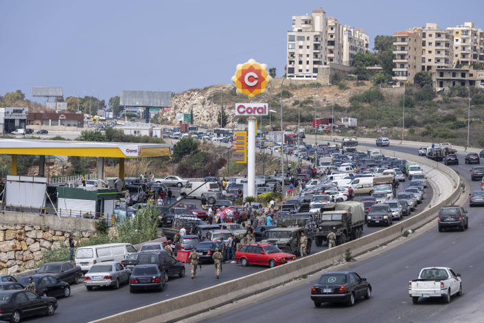 FILE - In this Sept. 3, 2021, file photo, cars line up at a petrol station as they try to get gas on the main highway in the coastal town of Jiyeh, south of Beirut, Lebanon. Countries like Lebanon, Syria, Iraq, Lebanon and Yemen are all teetering on the brink of humanitarian catastrophe with an economic implosion that threatens to throw the region into even deeper turmoil. (AP Photo/ Hassan Ammar)