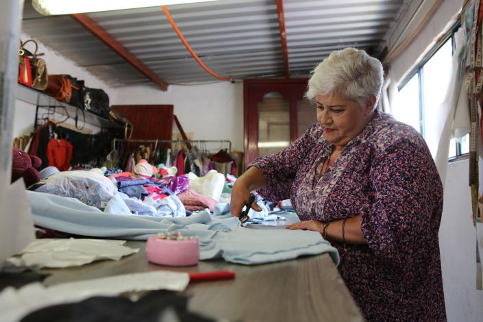 Seamstress Irma de la Parra cuts a T-shirt worn by a person who died from COVID-19, in her workshop in Mexico City, Saturday, April 24, 2021. De la Parra used to make teachers' gowns, but school closings during the pandemic left her without a job. She took it upon herself to make teddy bears out of clothing from those who died of COVID-19 to give those who are still alive a chance to grieve and be closer to those they were unable to bid farewell to. (AP Photo/Ginnette Riquelme)