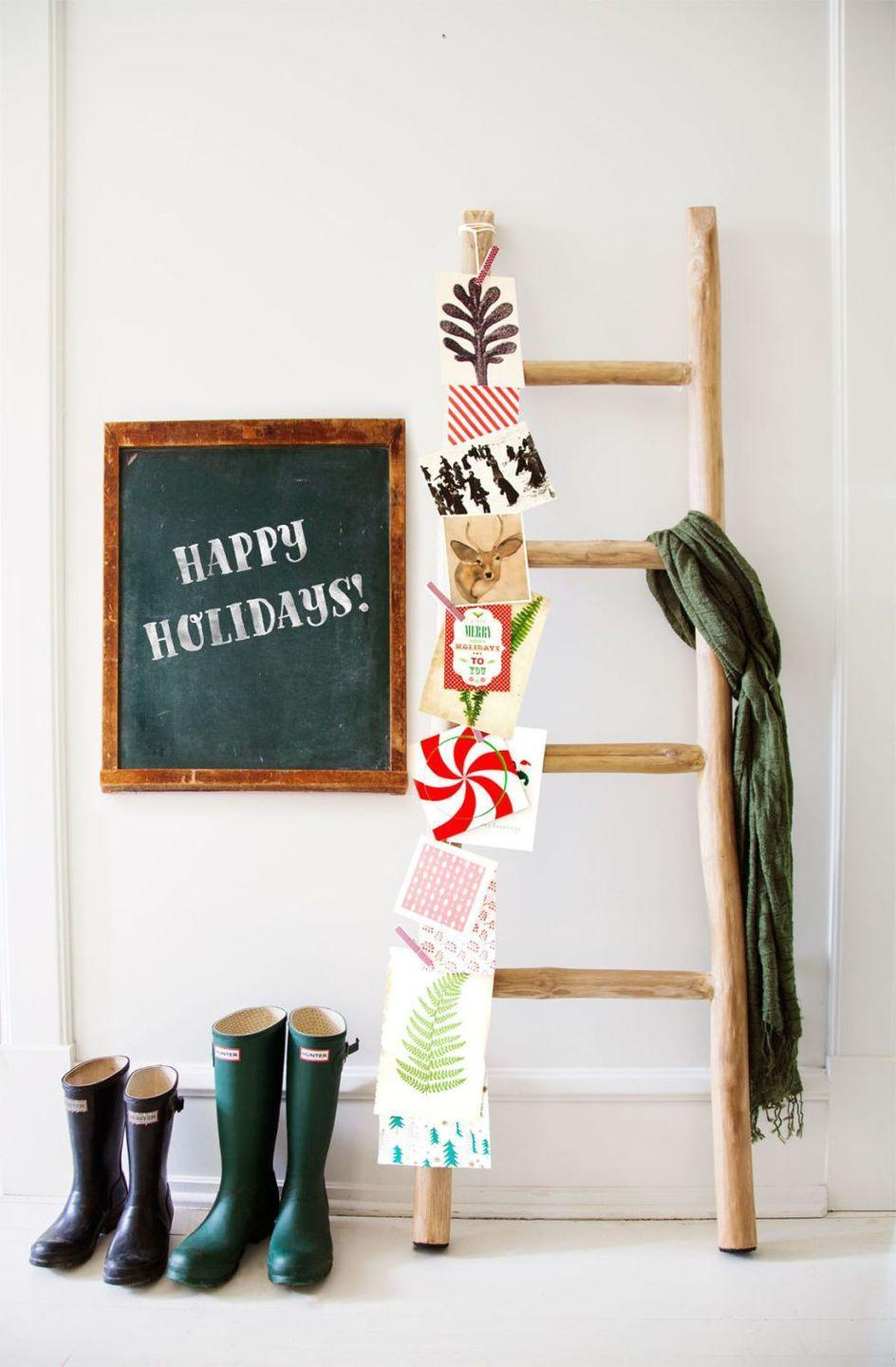 """<p>Pin holiday cards on a rustic ladder for a farmhouse-style Christmas display.</p><p>See more at <a href=""""https://www.countryliving.com/home-design/house-tours/g2780/jennaea-gearhart-white-christmas-decor/"""" rel=""""nofollow noopener"""" target=""""_blank"""" data-ylk=""""slk:Country Living"""" class=""""link rapid-noclick-resp"""">Country Living</a>.</p>"""