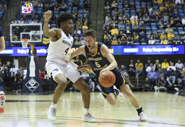 West Virginia's Miles McBride, left, defends Northern Colorado's Sam Masten, right, as he drives it up court during the first half of an NCAA college basketball game Monday Nov. 18, 2019, Morgantown, W.Va. (AP Photo/Kathleen Batten)
