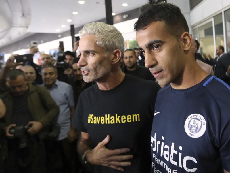 Refugee soccer player Hakeem Al-Araibi, right, arrives in Melbourne, Australia, Tuesday, Feb. 12, 2019, flanked by former Australia national team captain Craig Foster. Al-Araibi returned to Australia after the threat of extradition to Bahrain was lifted and three months after he was detained in Thailand. (David Crosling/AAP Image via AP)