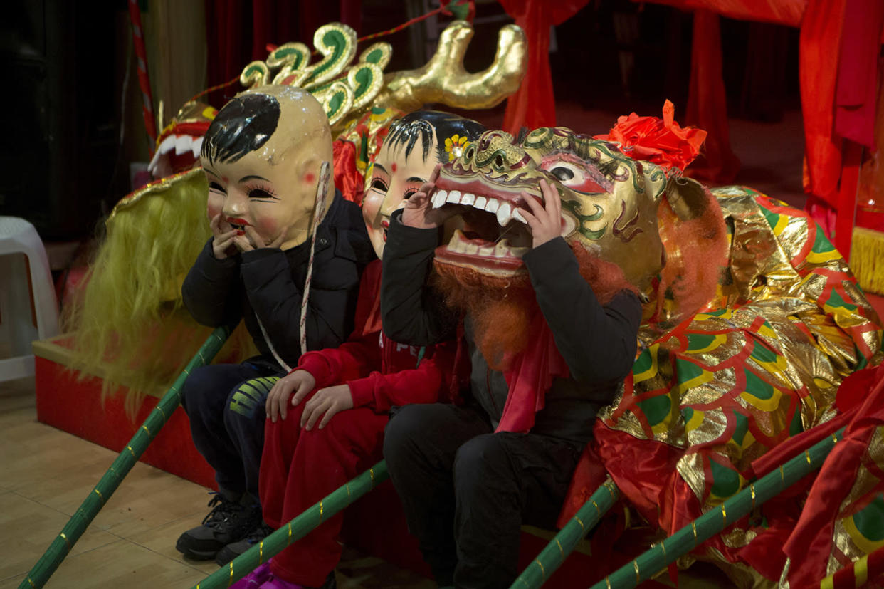 Children get ready for a parade during the Chinese community celebrations of the Lunar New Year, the year of the Rooster, in Madrid, Spain Saturday Jan. 28, 2017. (AP Photo/Paul White)