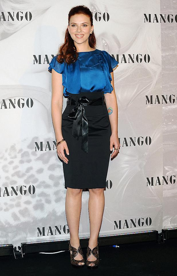 """Megan, however, wasn't the only Hollywood hottie dressed to impress while in Europe. Scarlett Johansson sported a super cute blue satin blouse, a black high-waisted skirt, and a smile while attending a press conference in Madrid. Fotonoticias/<a href=""""http://www.wireimage.com"""" target=""""new"""">WireImage.com</a> - July 13, 2009"""