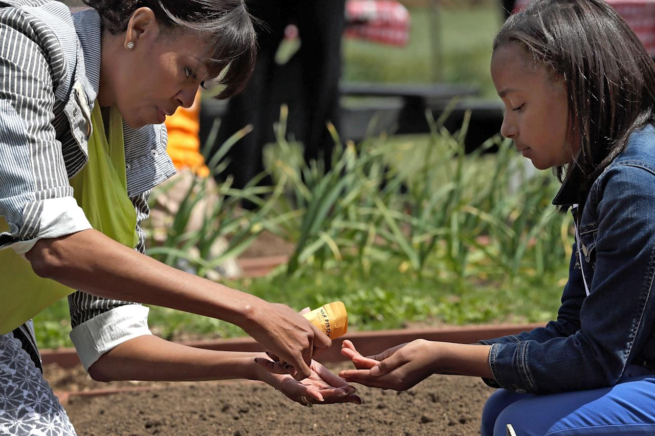 "WASHINGTON, DC - APRIL 04:  U.S. first lady Michelle Obama shares a packet of seeds as she plants the White House Kitchen Garden on the South Lawn of the White House April 4, 2013 in Washington, DC. For the fifth time, the first lady invited students from ""schools that have made exceptional improvements to school lunches"" from Florida, Massachusetts, Tennessee and Vermont to help her plant the garden.  (Photo by Win McNamee/Getty Images)"