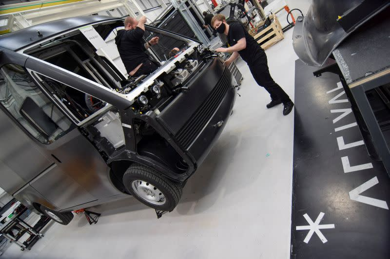 Workers build a fully-electric test van at electric van and bus maker Arrival Ltd, in Banbury